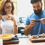 couple photographs their food in restaurant